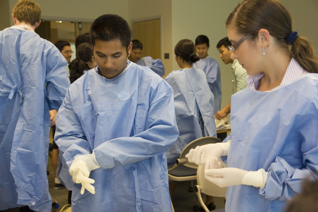 Medical students putting on gloves